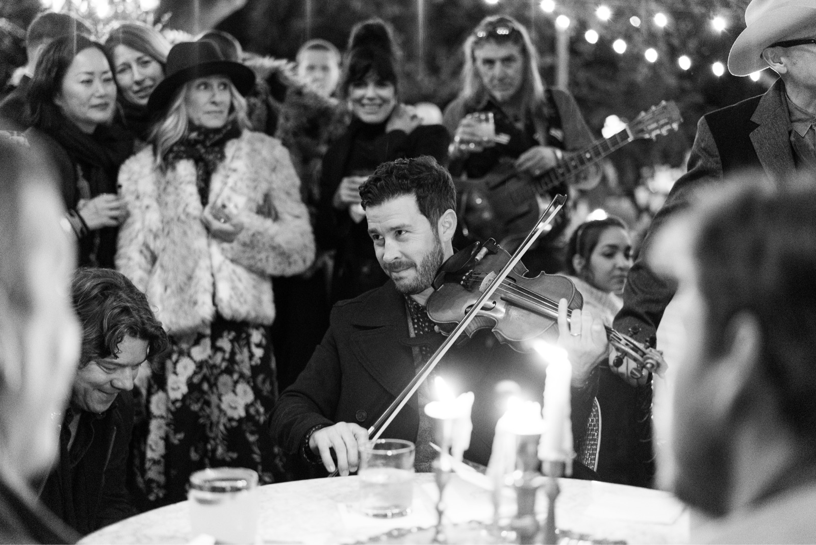 Man smiling and playing a violin while sitting at a dining table with onlookers