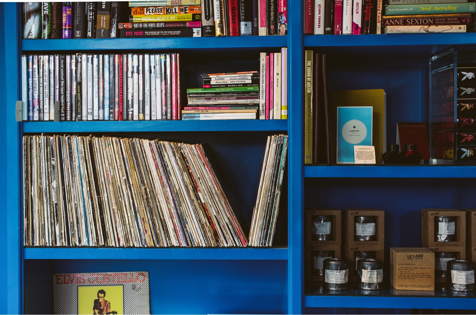 Library shelf with records, books, movies, candles