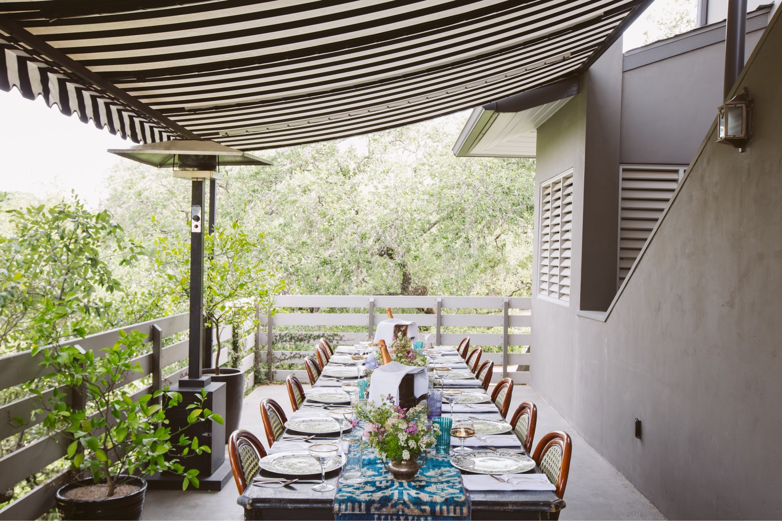 Outdoor long dining table under a stripped fabric awning